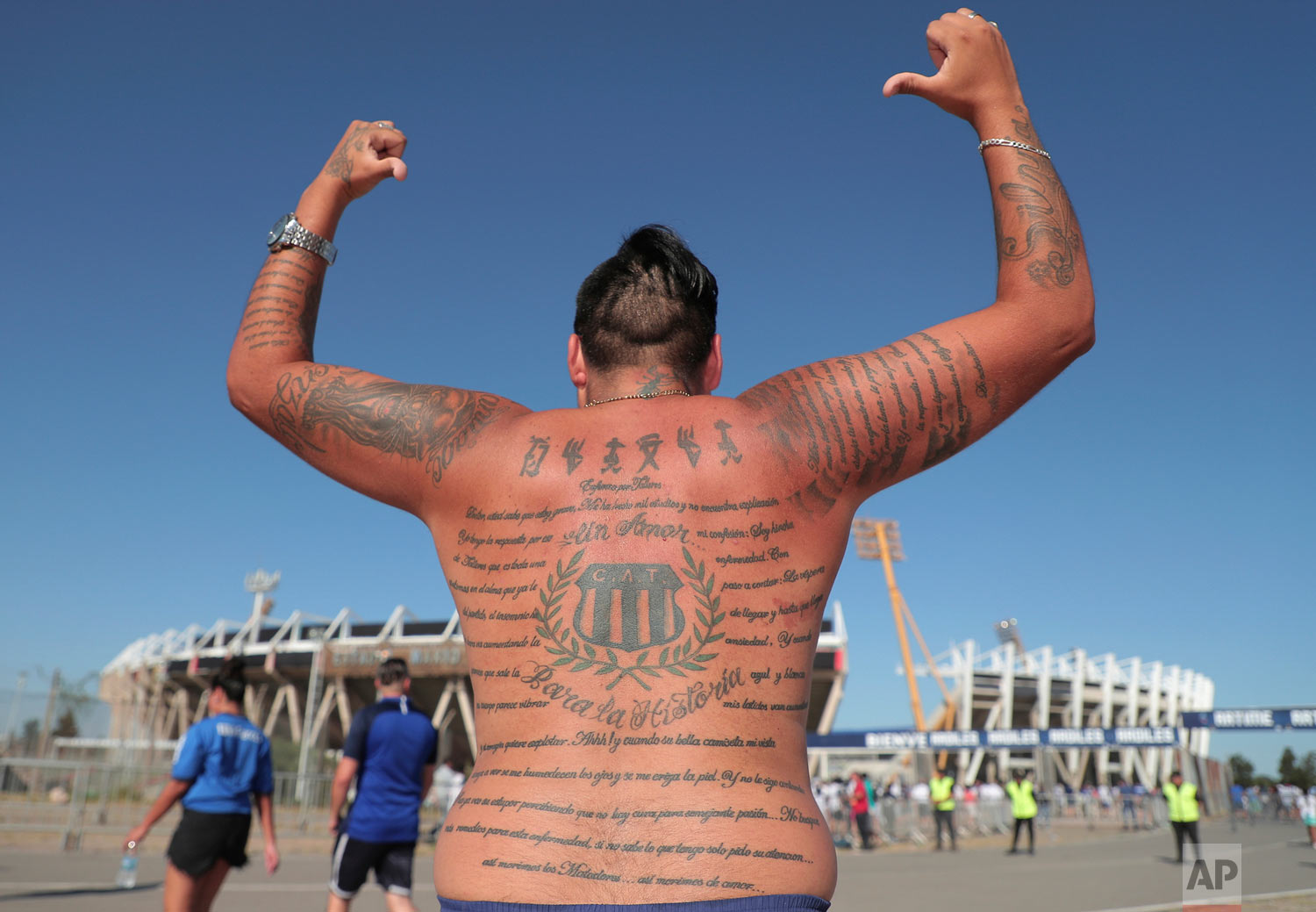 A fan of Argentina's Talleres soccer team shows off his soccer team related tattoo before attending a Copa Libertadores soccer match against Chile's Palestino in Cordoba, Argentina, Feb. 20, 2019. (AP Photo/Nicolas Aguilera)