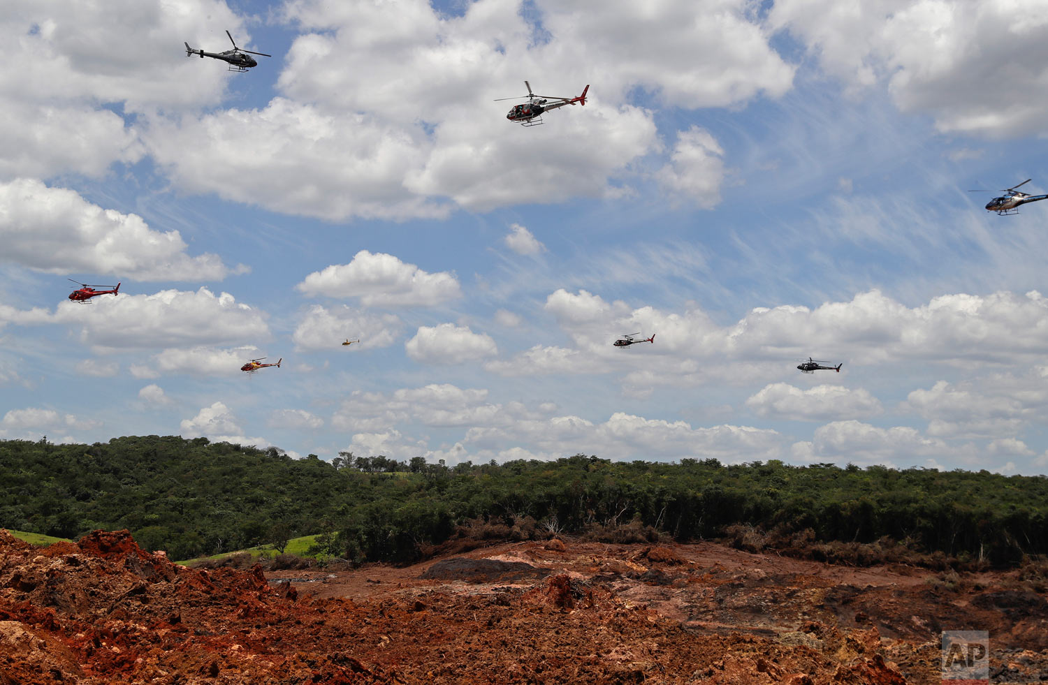 Helicopters hover over an iron ore mining complex to release thousands of flower petals paying homage to the dozens of victims killed and scores of missing after a mining dam collapsed there, in Brumadinho, Brazil, Feb. 1, 2019. (AP Photo/Andre Penner)