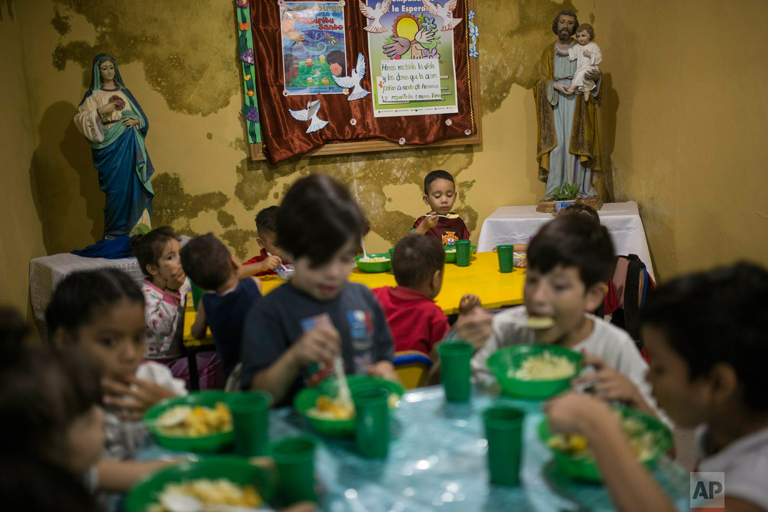 Children have lunch in San Antonio de Padua soup kitchen in the Petare slum, in Caracas, Venezuela, Feb. 11, 2019. (AP Photo/Rodrigo Abd)