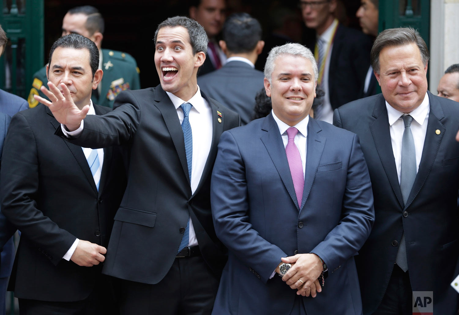 Venezuela's self-proclaimed interim president Juan Guaido waves flanked by Guatemala's President Jimmy Morales, from left, Colombia's President Ivan Duque and Panama's President Juan Carlos Varela as they gather for a group photo after attending an emergency Lima Group meeting concerning Venezuela, in Bogota, Colombia, Feb. 25, 2019. (AP Photo/Martin Mejia)