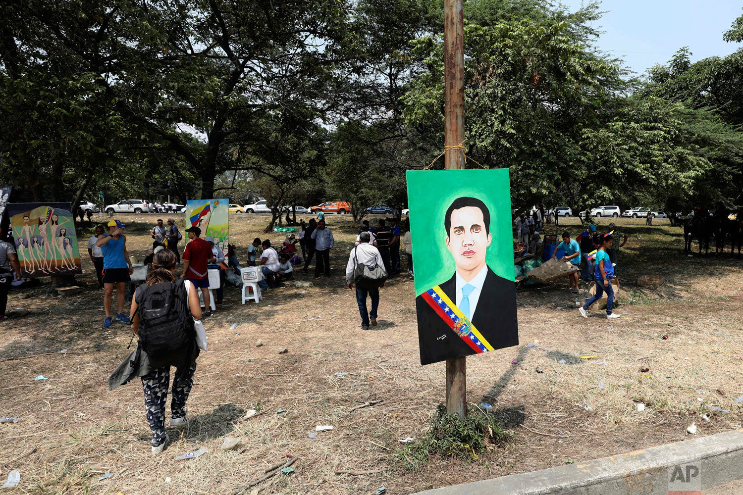 A painting of Venezuela's self-proclaimed interim president Juan Guaido wearing the presidential sash, hangs from a post at the Tienditas International Bridge on the outskirts of Cucuta, Colombia, on the border with Venezuela, Feb. 23, 2019. (AP Photo/Fernando Vergara)