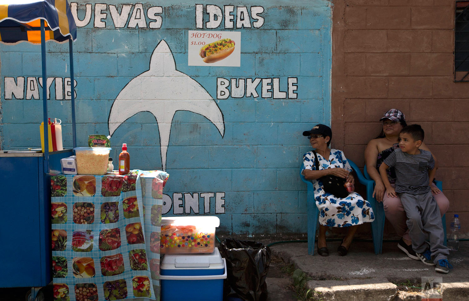 Neighbors sits next to a campaign mural promoting presidential frontrunner Nayib Bukele, of the Grand National Alliance for Unity, on the outskirts of San Salvador, El Salvador, Feb. 1, 2019. Bukele, a young businessman and former mayor of El Salvador's capital, was elected as El Salvador's new president. (AP Photo/Moises Castillo