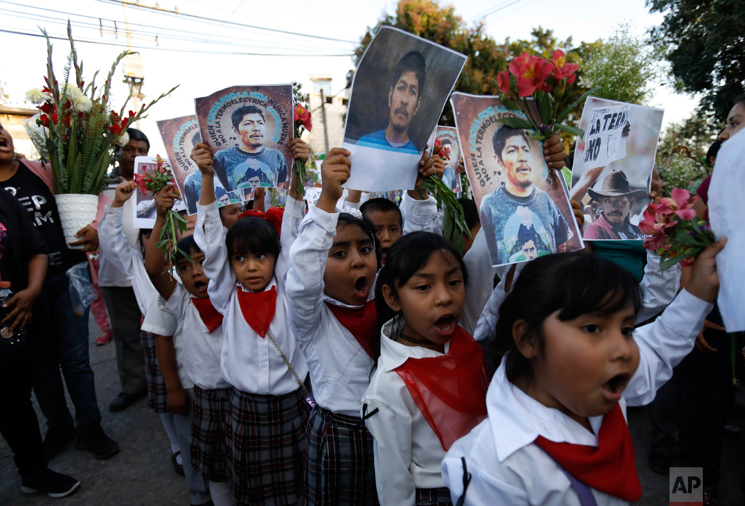 Children carry pictures of murdered community activist Samir Flores Soberanes as they accompany the coffin that contains his remains, in Amilcingo, Mexico, Feb. 21, 2019. (AP Photo/Rebecca Blackwell)