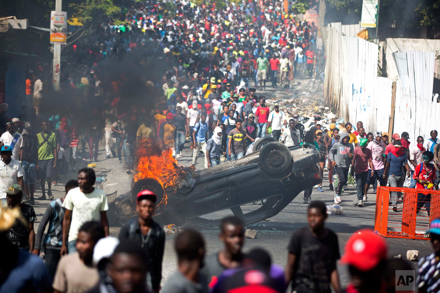 Protesters march past an overturned burning car, as they demand the resignation of Haitian President Jovenel Moise in Port-au-Prince, Haiti, Feb. 12, 2019. (AP Photo/Dieu Nalio Chery)