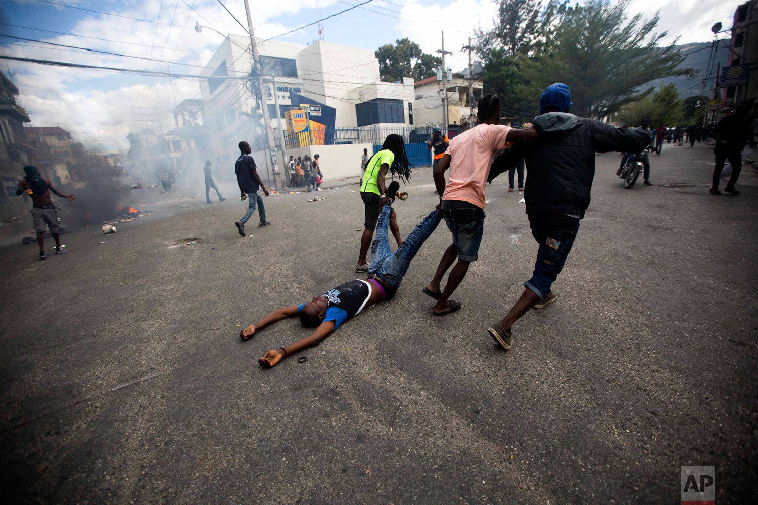 Demonstrators drag the body of an unidentified protester toward police, as a form of protest after police shot into the crowd killing the unidentified protester, during a demonstration demanding the resignation of Haitian President Jovenel Moise near the presidential palace in Port-au-Prince, Haiti, Feb. 12, 2019. (AP Photo/Dieu Nalio Chery)