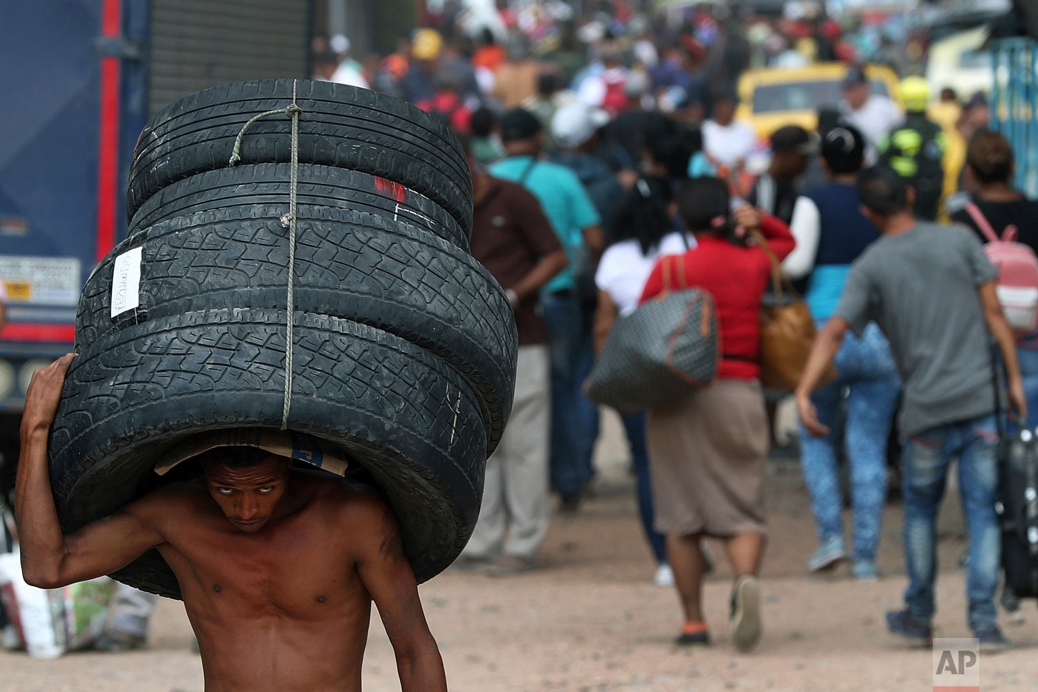 A man hauls used tires back to Venezuela, using a blind spot on the border near the closed Simon Bolivar International Bridge, in La Parada, Colombia, Feb. 28, 2019. (AP Photo/Martin Mejia)