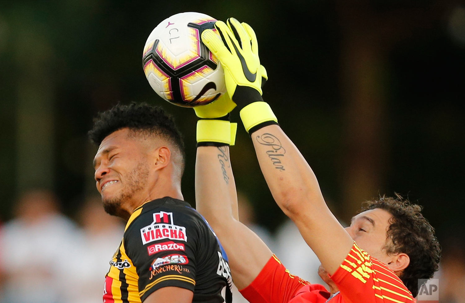 Paraguay's Libertad goalkeeper Martin Silva catches the ball preventing Bolivia's The Strongest Rolando Blackburn from heading the ball during a Copa Libertadores soccer game, in Asuncion, Paraguay, Feb. 13, 2019. (AP Photo/Jorge Saenz)