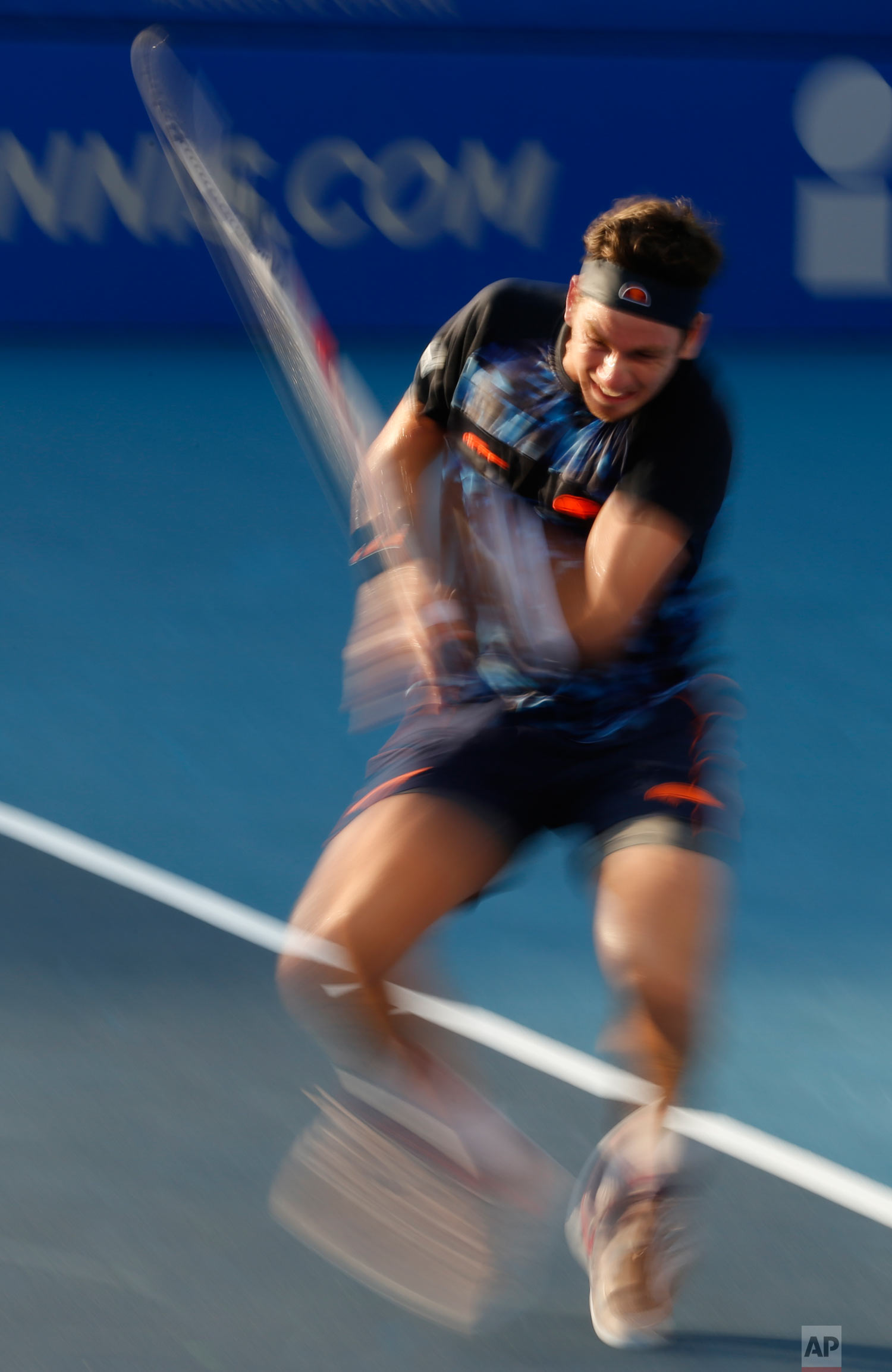 In this photo taken with a slow shutter speed, Great Britain's Cameron Norrie returns a ball in his Mexican Tennis Open quarterfinal match against Mackenzie McDonald of the U.S., in Acapulco, Mexico, Feb. 28, 2019. (AP Photo/Rebecca Blackwell)