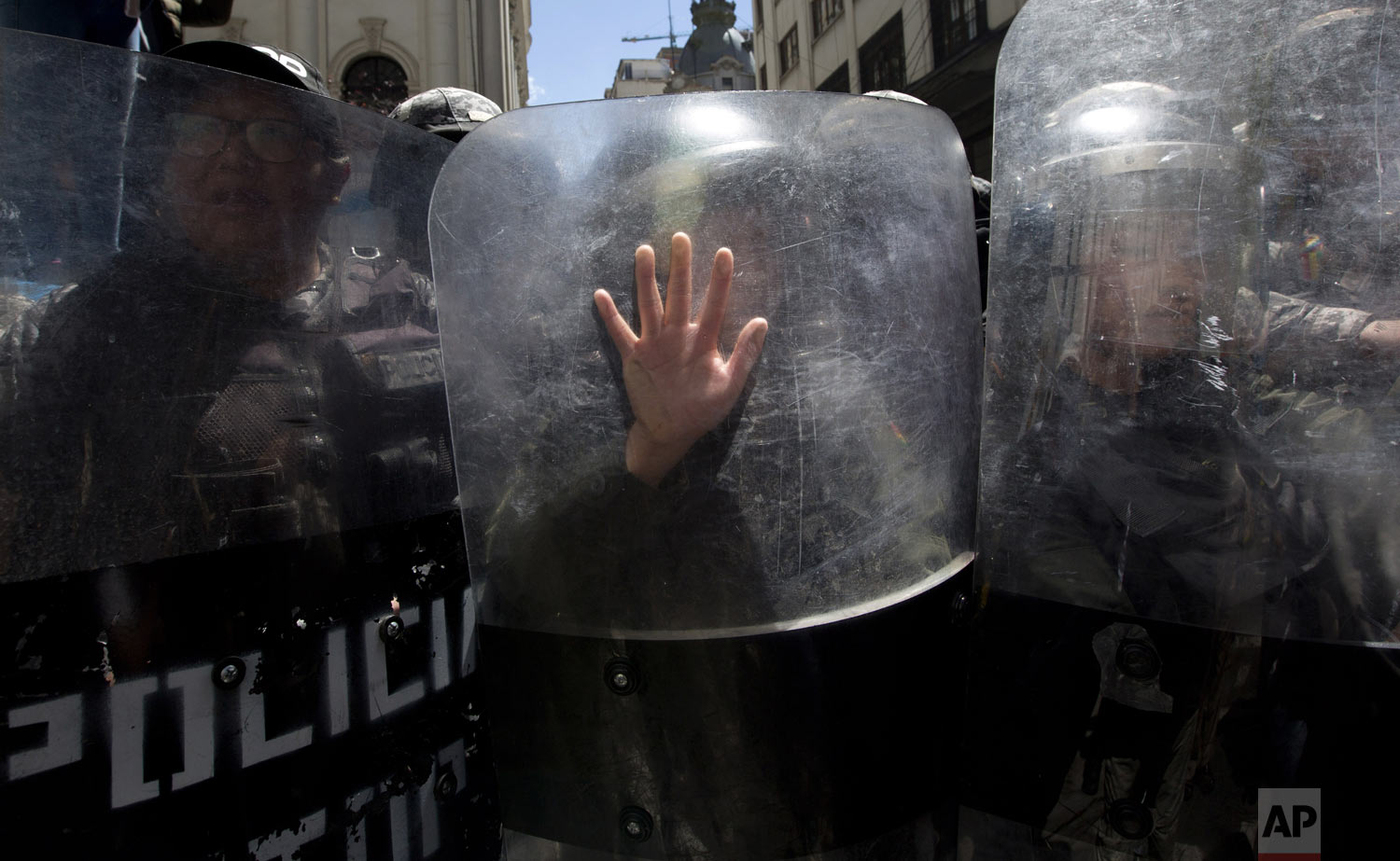 A riot police officer places her hand on her shield as she helps to prevent a march marking International Women's Day from reaching the government palace, in La Paz, Bolivia, on Friday, March 8, 2019. The day has been sponsored by the United Nations since 1975 as millions of women around the world are demanding equality amid a persistent salary gap, violence and widespread inequality. (AP Photo/Juan Karita)