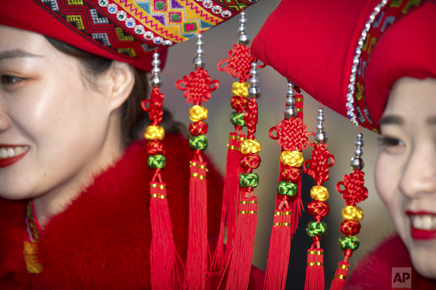 Decorations dangle from the hats of bus ushers in ethnic minority dress as they pose for a group photo during the opening session of China's National People's Congress (NPC) at the Great Hall of the People in Beijing on Tuesday, March 5, 2019. (AP Photo/Mark Schiefelbein)