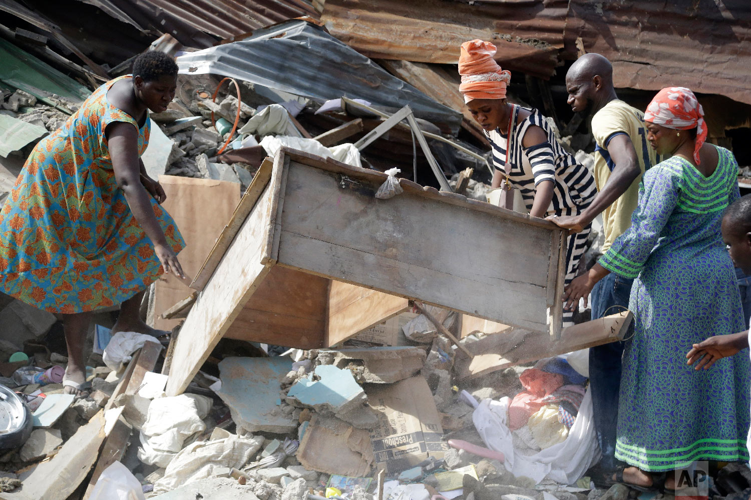 Local people look through debris at the scene after a building collapsed in Lagos, Nigeria, Thursday, March 14, 2019. (AP Photo/Sunday Alamba)