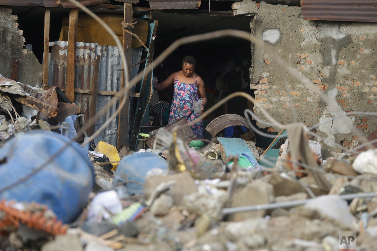 A woman looks at the scene after a building collapsed in Lagos, Nigeria, Thursday, March 14, 2019. (AP Photo/Sunday Alamba)