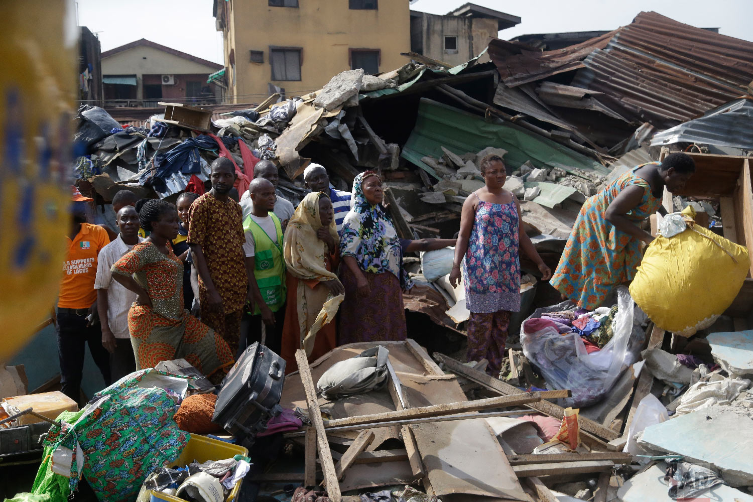 Local people at the scene after a building collapsed in Lagos, Nigeria, Thursday, March 14, 2019. (AP Photo/Sunday Alamba)