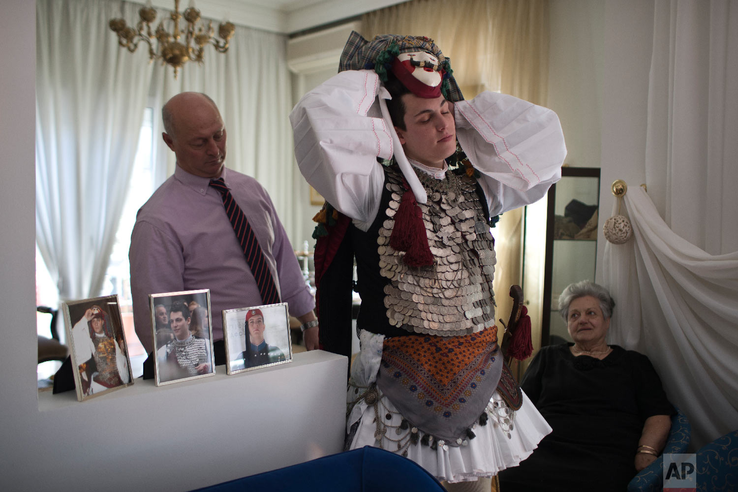 A dancer gets dressed at his home as he prepares to compete in the Boules and Genitsaroi carnival parade in the town of Naousa, northern Greece on March 10, 2019. (AP Photo/Petros Giannakouris)