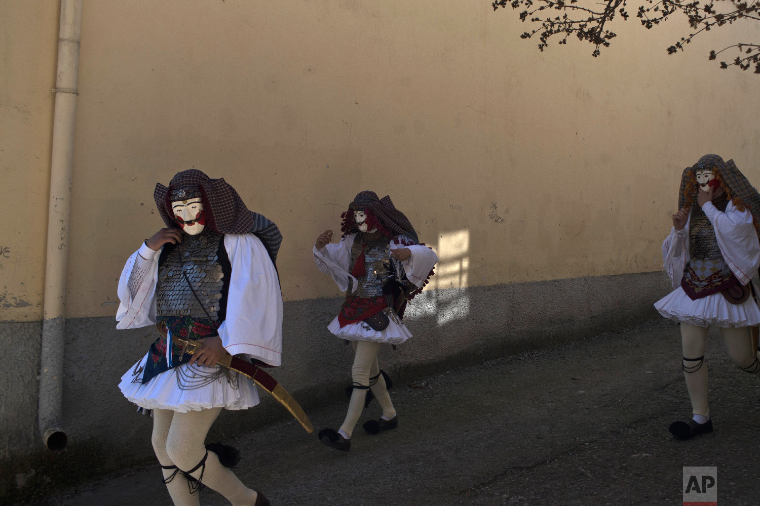 Dancers with masks and traditional costume prepare to perform in the Boules and Genitsaroi carnival parade in the town of Naousa, northern Greece on March 10, 2019. (AP Photo/Petros Giannakouris)