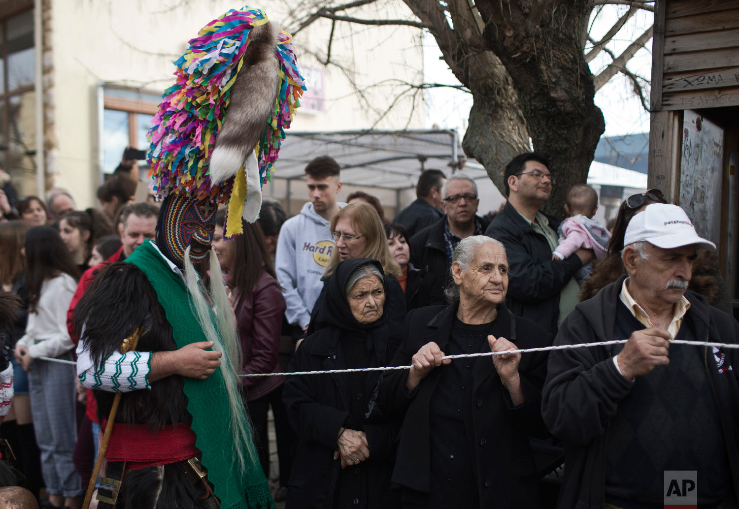 Spectators look on as a man wearing a goat hide with bells around his waist and a mask that includes a meter tall, ribbon-covered formation topped with a foxtail, also called a bell wearer, participates in a Clean Monday festival in the village of Sohos, northern Greece on March 11, 2019. (AP Photo/Petros Giannakouris)