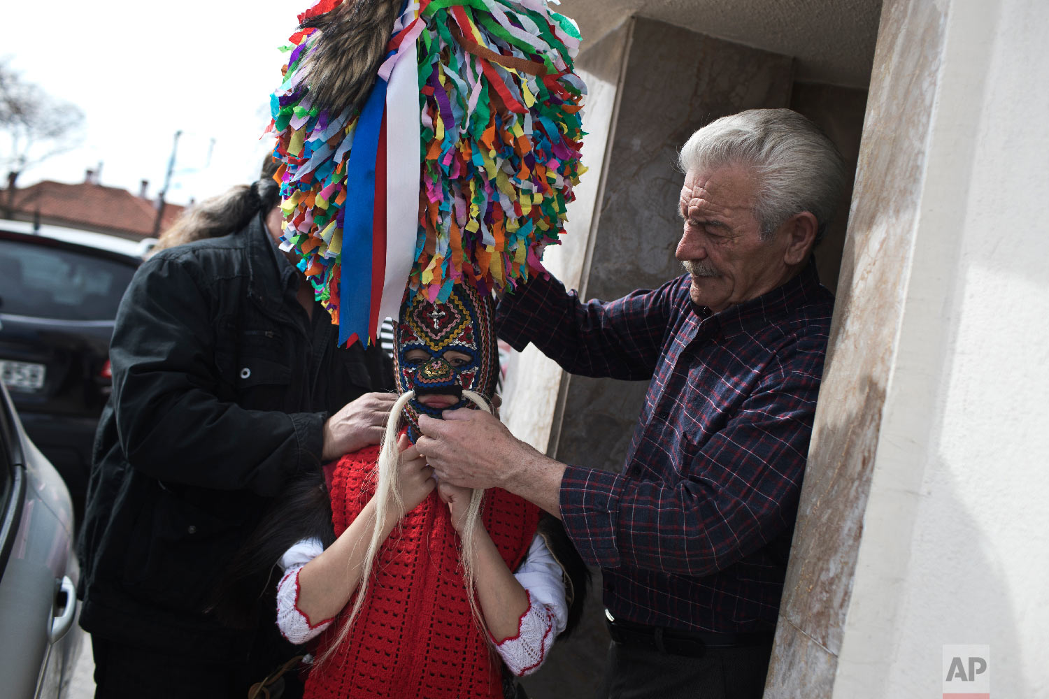 A grandfather helps a young bell wearer with the costume in the village of Sohos, northern Greece, to participate in a Clean Monday festival on March 11, 2019. (AP Photo/Petros Giannakouris)