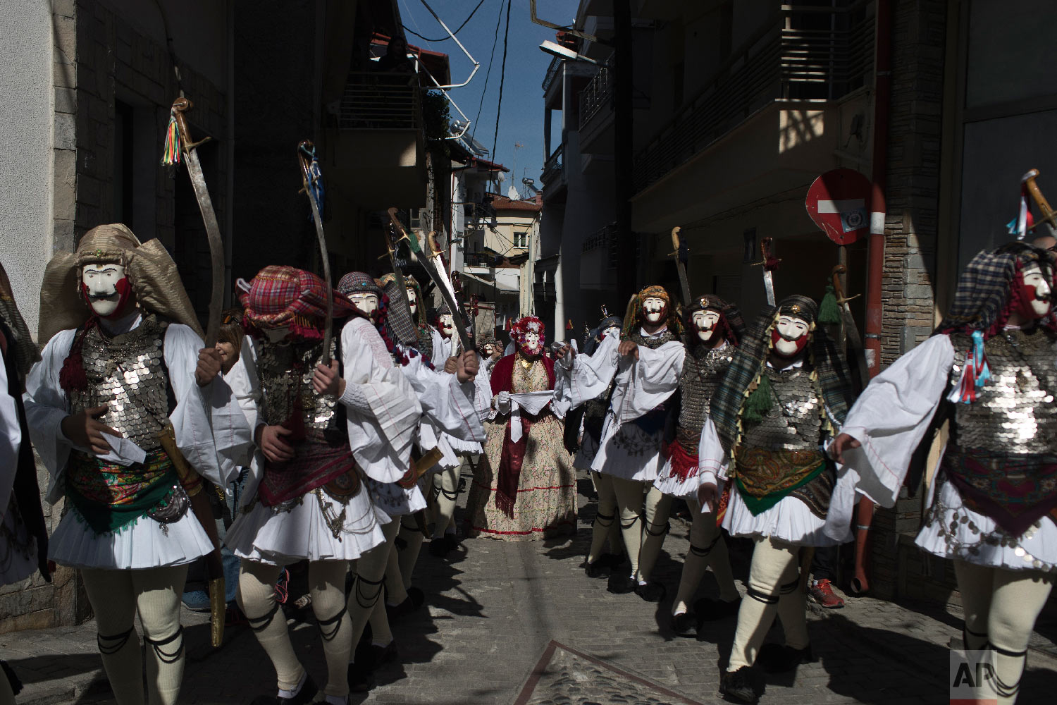 Dancers with masks and traditional costumes perform in the Boules and Genitsaroi carnival parade in the town of Naousa, northern Greece on March 10, 2019. (AP Photo/Petros Giannakouris)