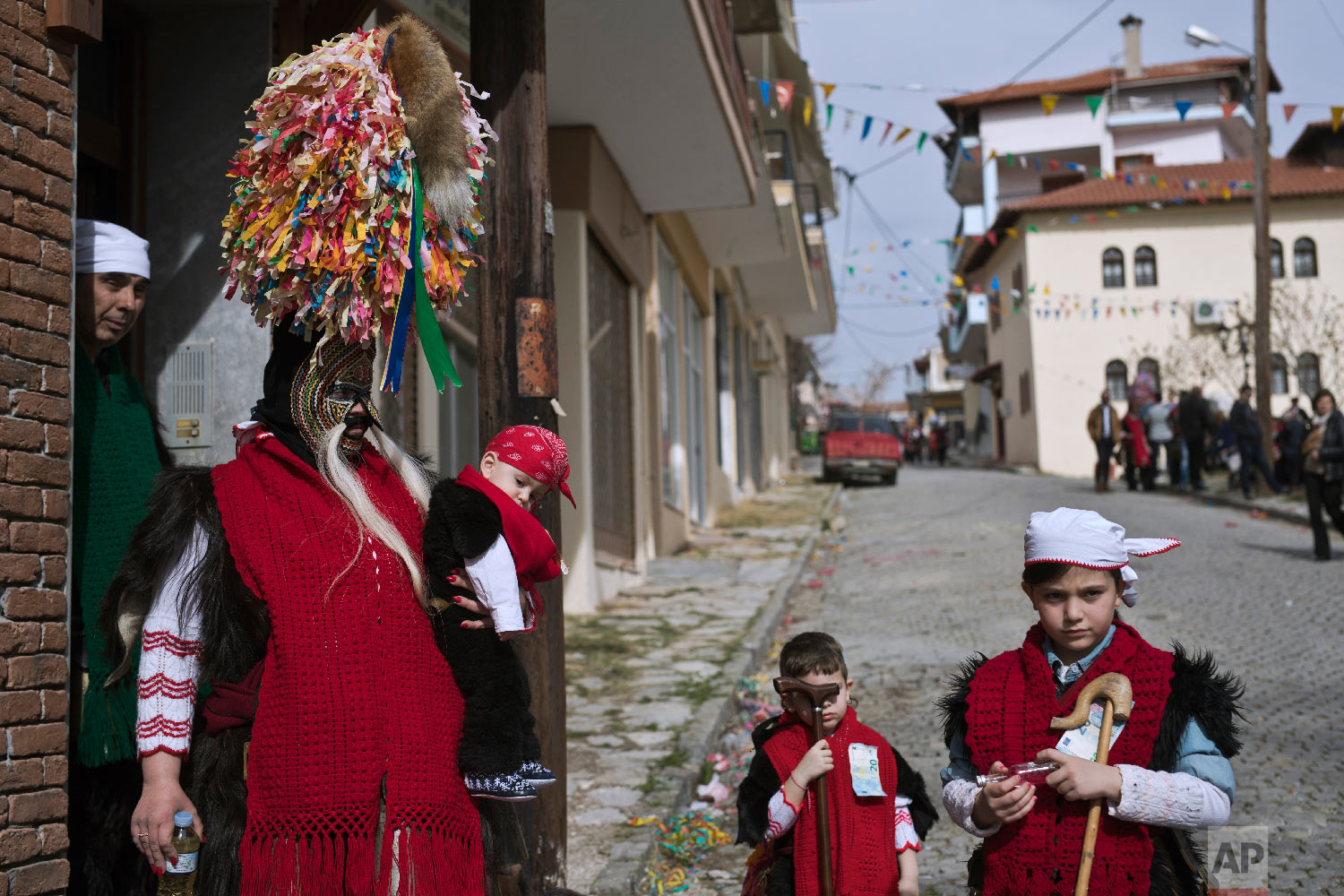 A mother wearing goat hide with bells around here waist and a mask that includes a meter tall, ribbon-covered formation topped with a foxtail, holds her baby as her five member family prepare to take part in a Clean Monday festival in the village of Sohos, northern Greece on March 11, 2019. (AP Photo/Petros Giannakouris)