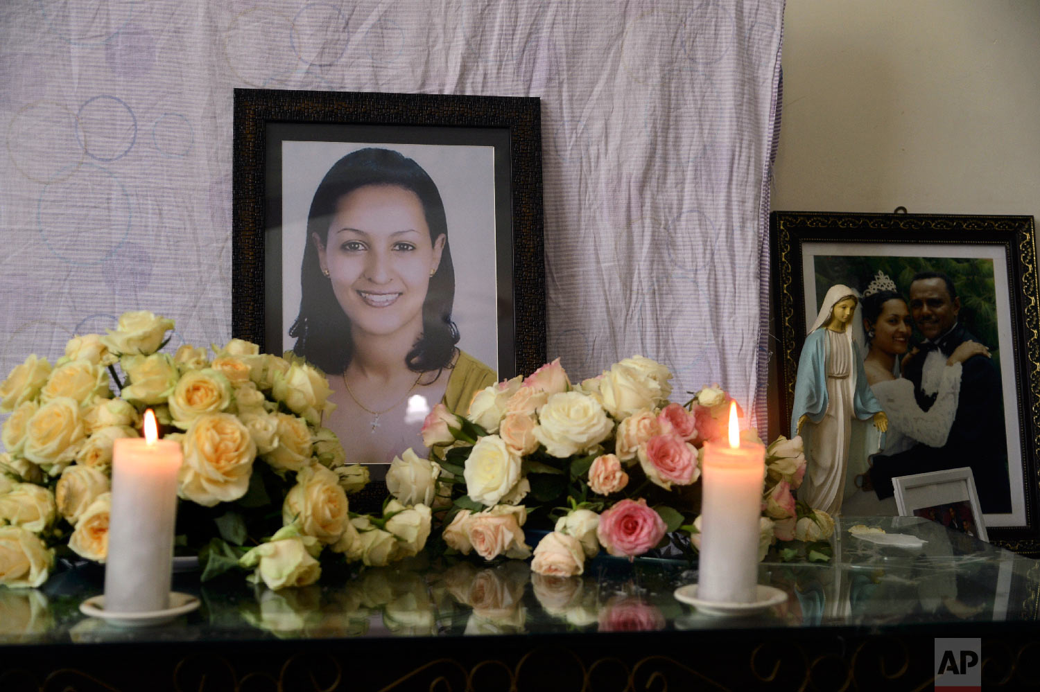 Candles burn in front of the photo of crash victim air hostess Sara Gebremichael, 38, at her house in Addis Ababa, Ethiopia, March 13 2019. (AP Photo/Samuel Habtab)