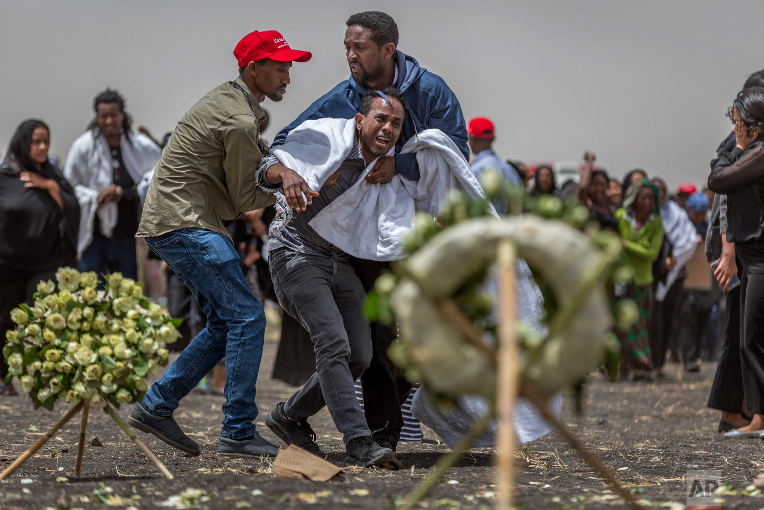 Ethiopian relatives of crash victims mourn and grieve at the scene where the Ethiopian Airlines Boeing 737 Max 8 crashed shortly after takeoff on Sunday near Bishoftu, Ethiopia on March 14, 2019. (AP Photo/Mulugeta Ayene)