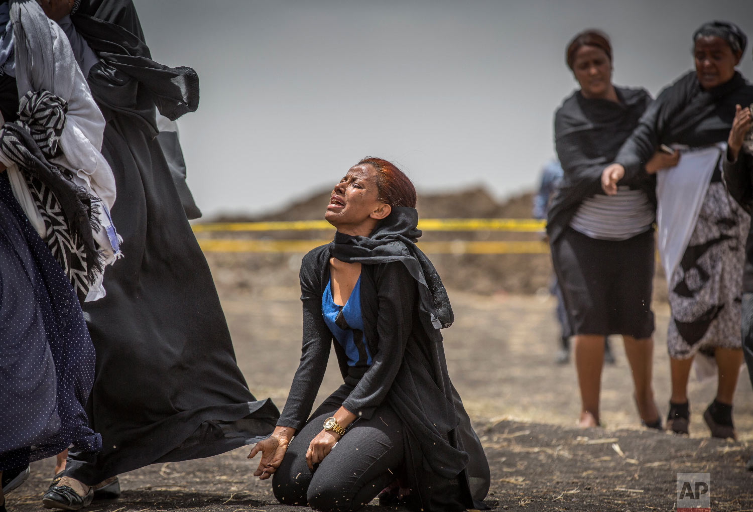 Ethiopian relatives of crash victims mourn and grieve at the scene where the Ethiopian Airlines Boeing 737 Max 8 crashed shortly after takeoff on Sunday near Bishoftu, Ethiopia, March 14, 2019. (AP Photo/Mulugeta Ayene)