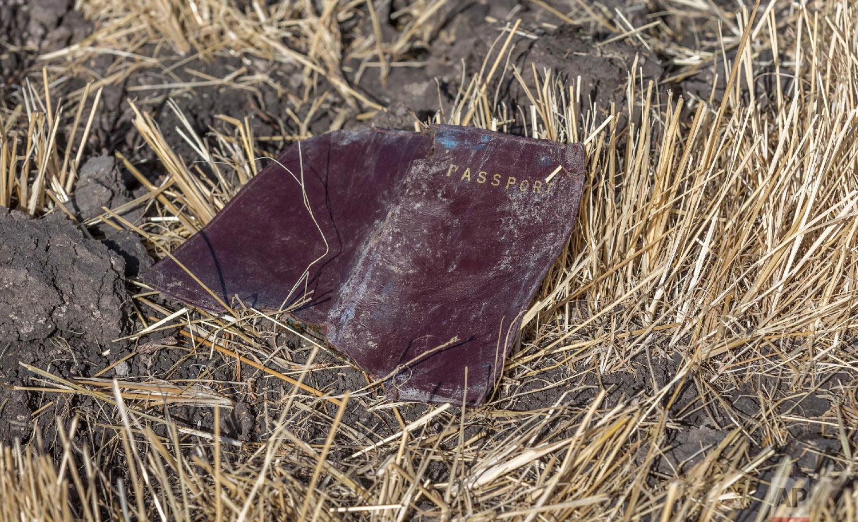 A passenger passport lies on the ground at the scene of an Ethiopian Airlines flight crash near Bishoftu, Ethiopia, March 11, 2019. (AP Photo/Mulugeta Ayene)