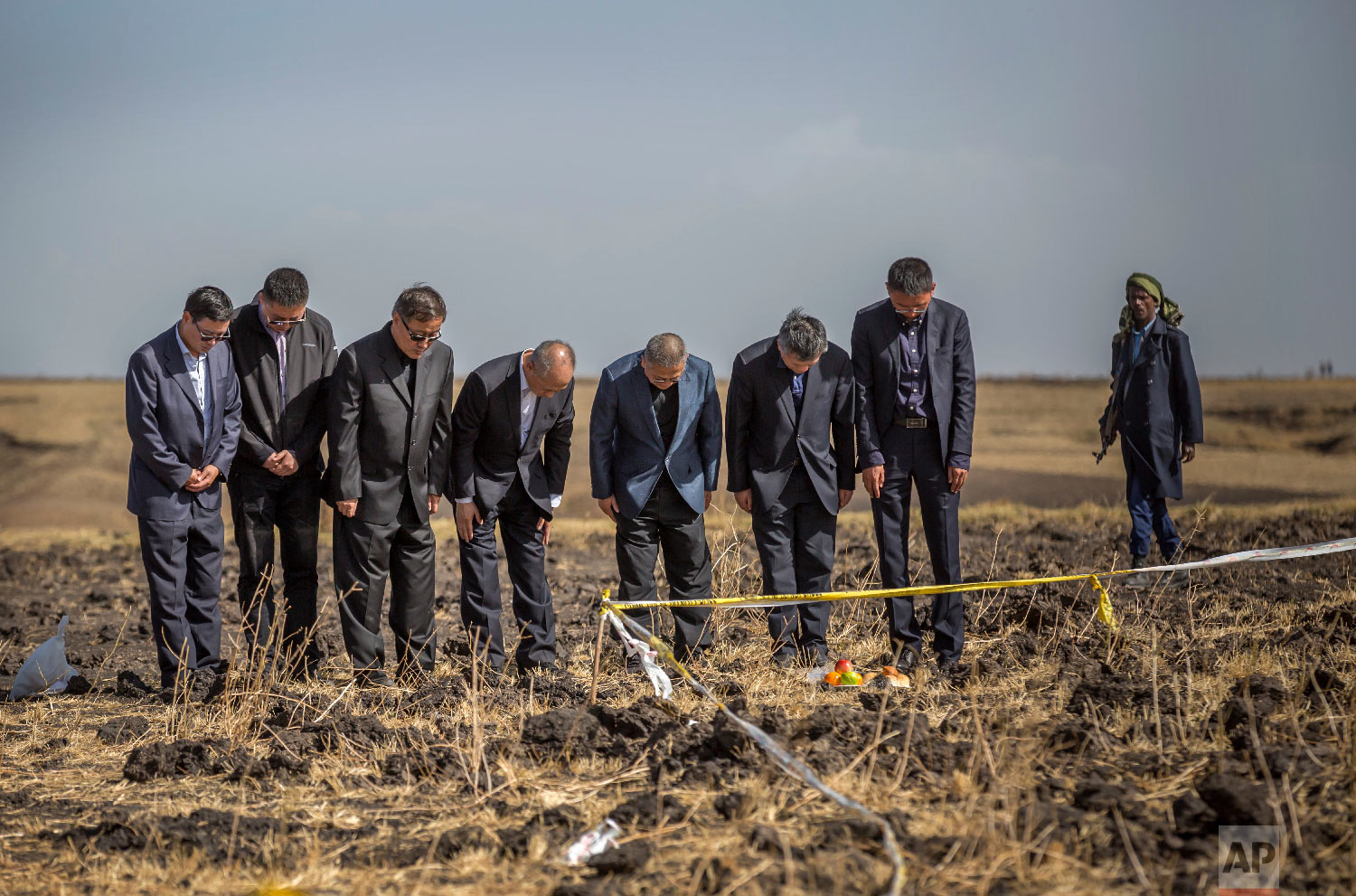 Officials from the Aviation Industry Corporation of China (AVIC) pray next to an offering of fruit, bread rolls, and a plastic container of Ethiopian Injera, a fermented sourdough flatbread, placed next to incense sticks, at the scene where the Ethiopian Airlines Boeing 737 Max 8 crashed shortly after takeoff on Sunday near Bishoftu, Ethiopia, March 12, 2019. (AP Photo/Mulugeta Ayene)