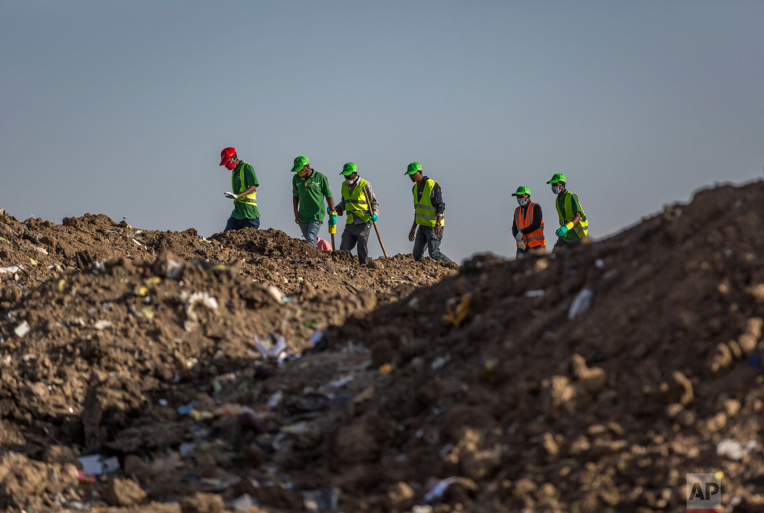 Workers walk to collect clothes and other materials, under the instruction of investigators March 12, 2019. (AP Photo/Mulugeta Ayene)