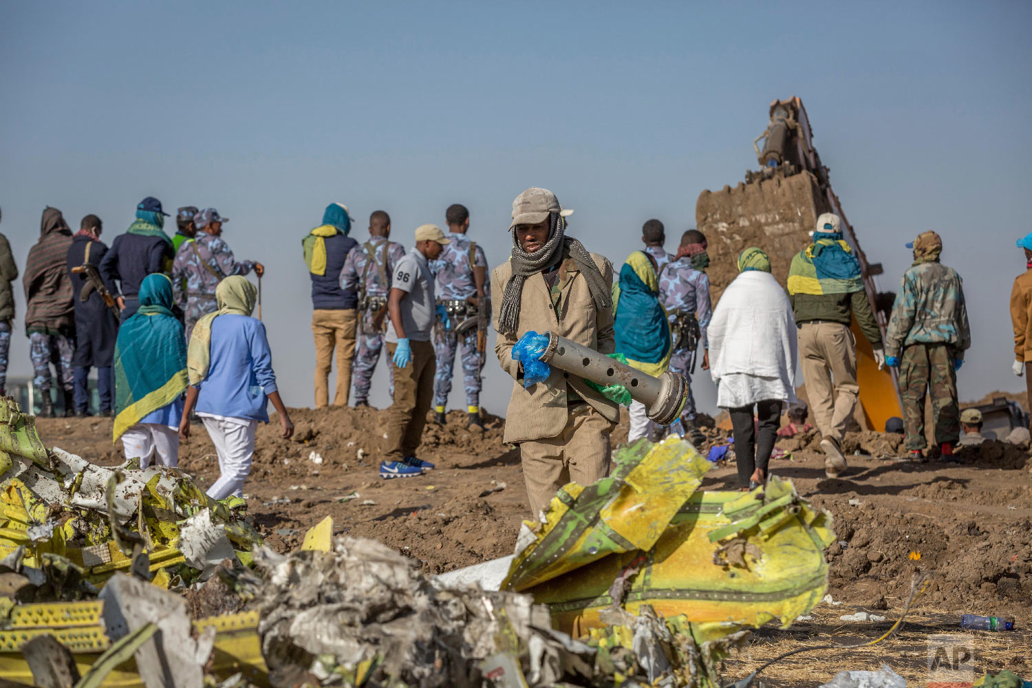 Workers gather at the scene of an Ethiopian Airlines flight crash near Bishoftu, Ethiopia, March 11, 2019. (AP Photo/Mulugeta Ayene)
