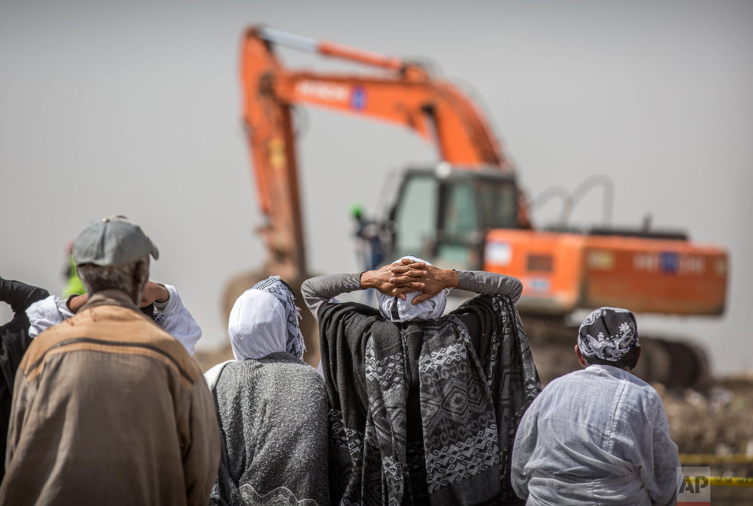 Ethiopian relatives of crash victims mourn as a mechanical digger operates at the scene where the Ethiopian Airlines Boeing 737 Max 8 crashed shortly after takeoff on Sunday near Bishoftu, Ethiopia, March 14, 2019. (AP Photo/Mulugeta Ayene)