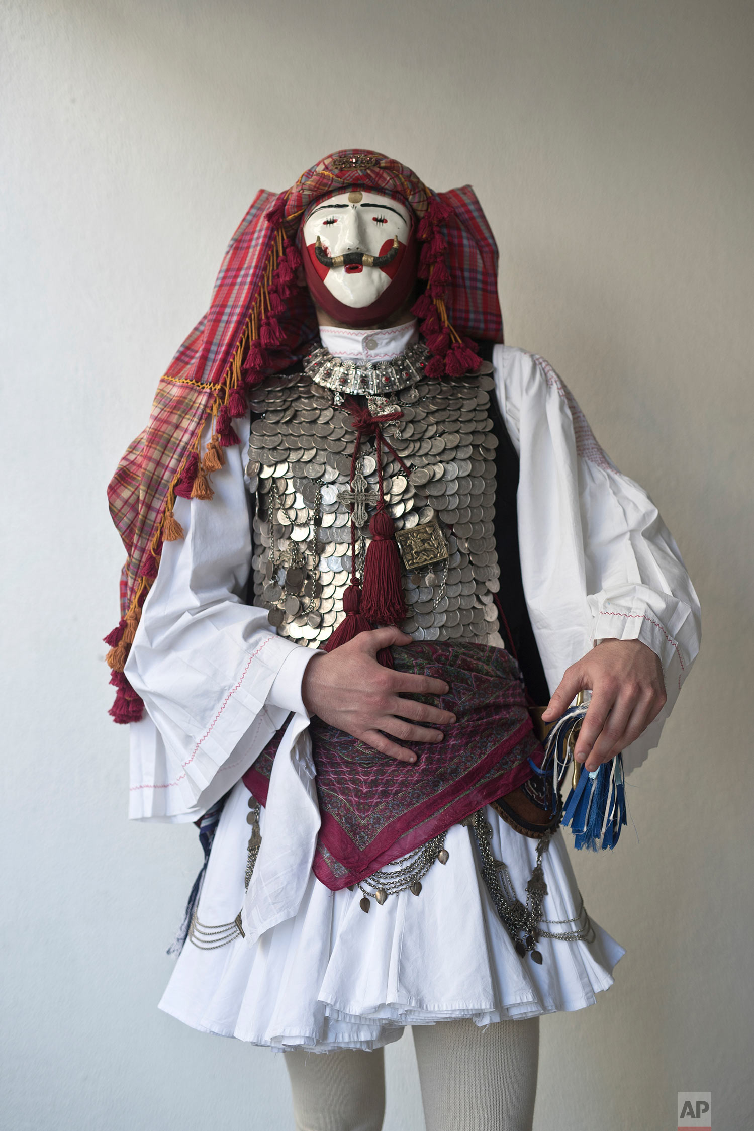 In this Sunday March 10, 2019 photo a dancer wearing a mask and traditional attire poses for a picture as he participates in the Boules and Genitsaroi carnival parade in the town of Naousa, northern Greece. (AP Photo/Petros Giannakouris)