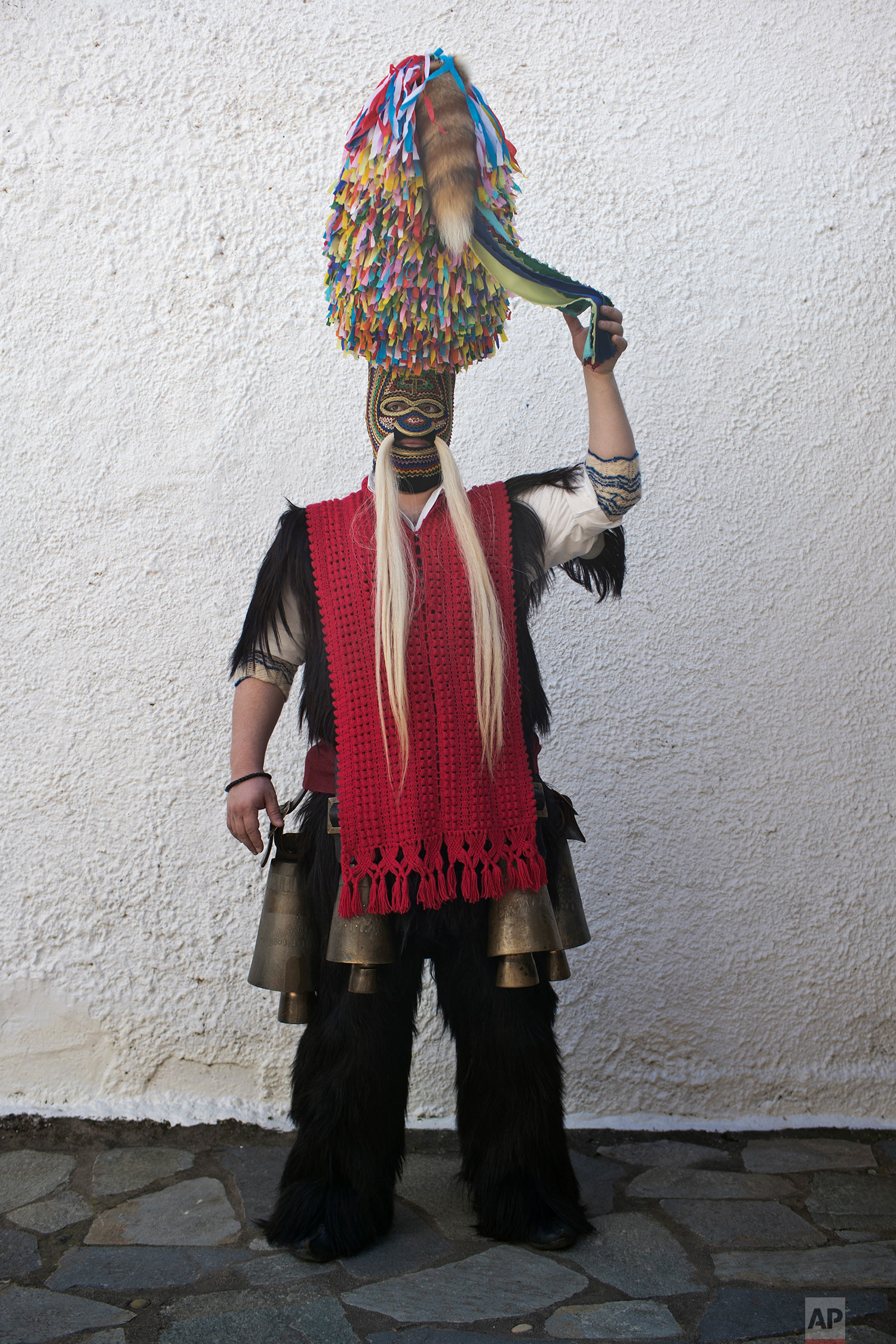 In this Monday March 11, 2019 a man wearing goat hide with bells around his waist and a mask that include a meter tall, ribbon-covered formation topped with a foxtail, also called bell wearer, poses for a picture in the village of Sohos, northern Greece, as he participates in a Clean Monday festival The procession is one of a great variety of customs across Greece. (AP Photo/Petros Giannakouris)