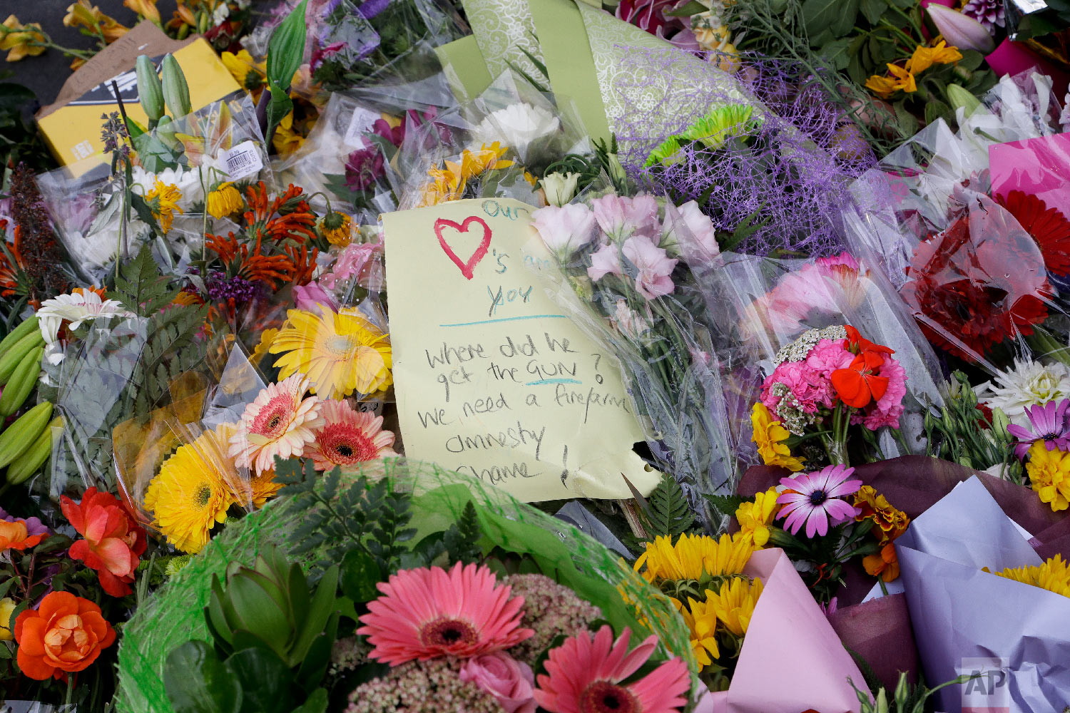 A handwritten message is placed at a collection of flowers left near the Masjid Al Noor mosque in Christchurch, New Zealand, Saturday, March 16, 2019, where one of the two mosque mass shootings at occurred. (AP Photo/Mark Baker)