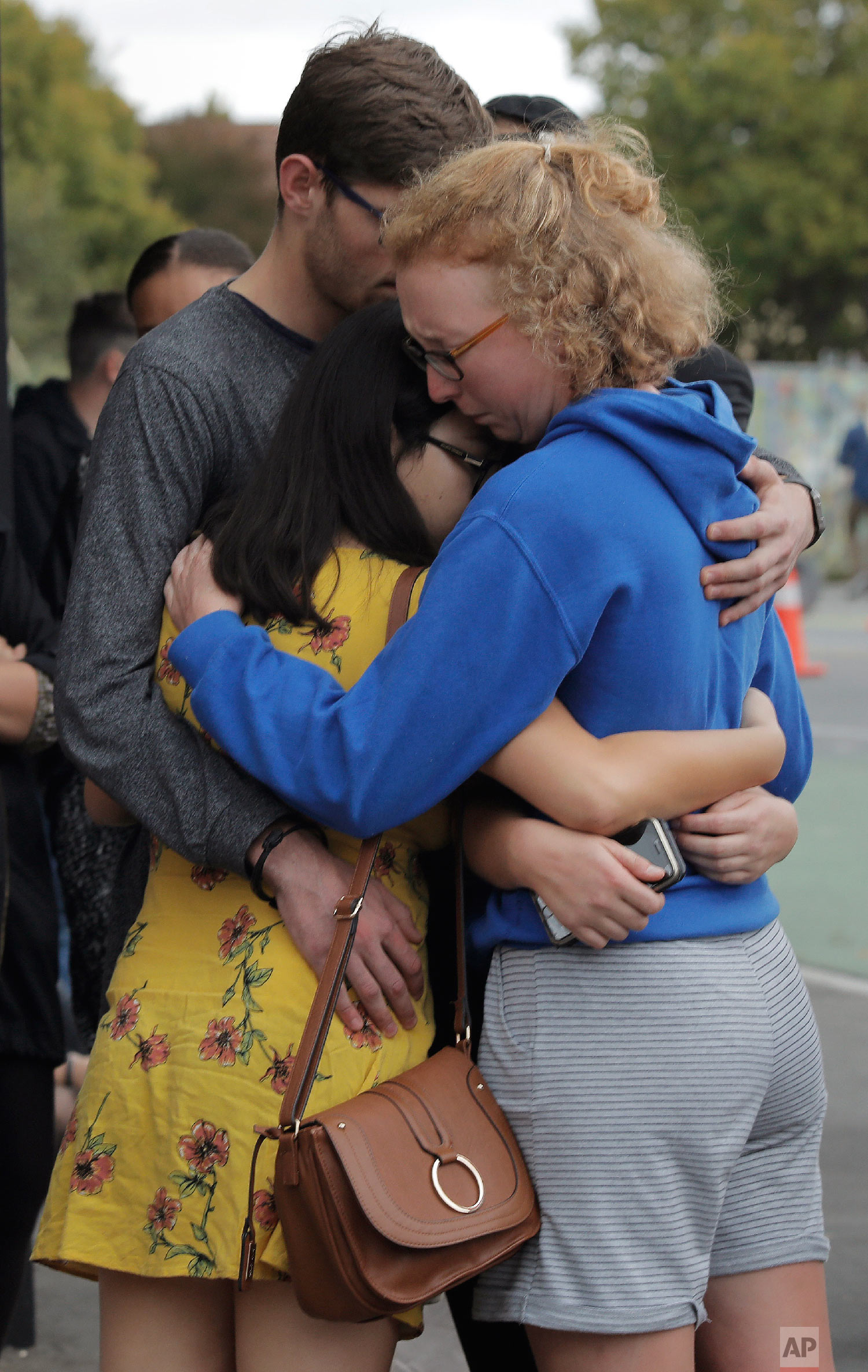 Mourners hug as they pay their respects at a makeshift memorial near the Masjid Al Noor mosque in Christchurch, New Zealand, Saturday, March 16, 2019, where one of the two mass shootings occurred.(AP Photo/Vincent Yu)