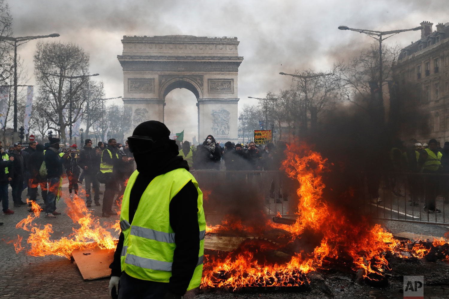 A yellow vest protester walks past a fire on the Champs Elysees avenue March 16, 2019, in Paris. (AP Photo/Christophe Ena)