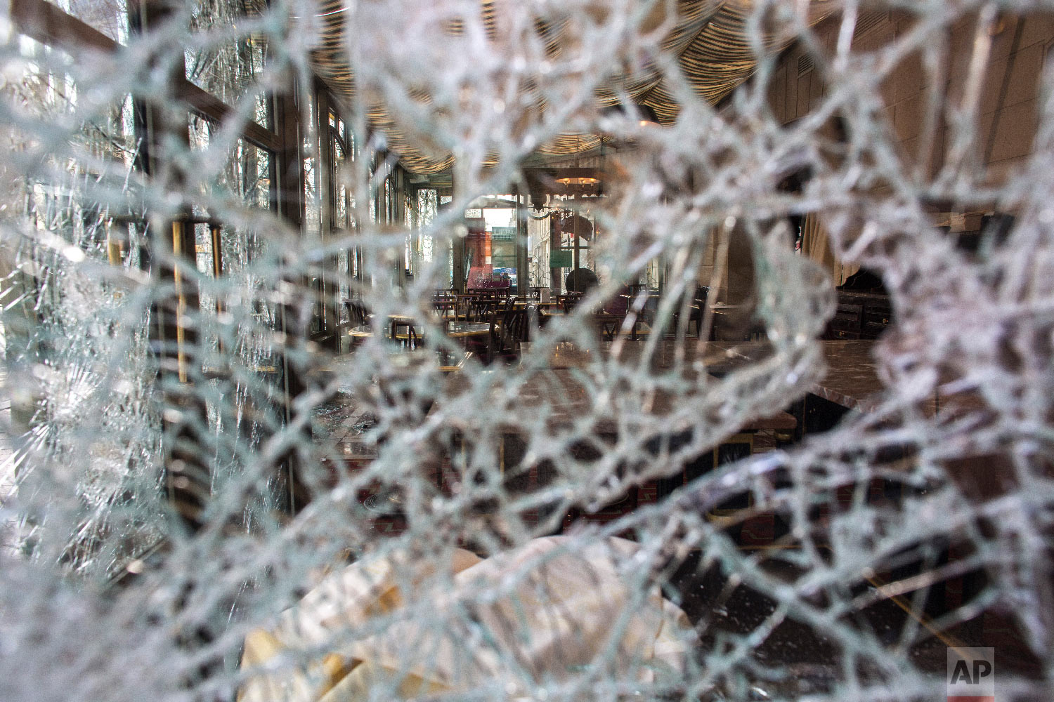 The inside view of the famed tea salon Laduree pictured through smashed windows the day after it was vandalized during the 18th straight weekend of demonstrations by the yellow vests, in Paris, March 17, 2019. (AP Photo/Rafael Yaghobzadeh)