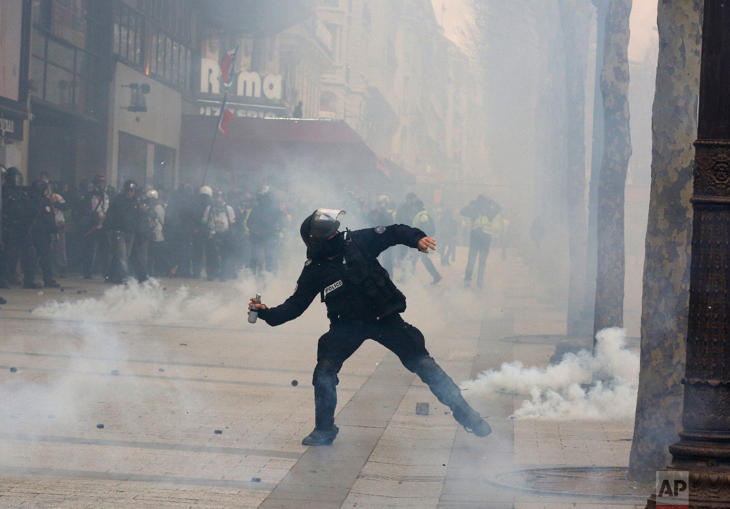 A riot police officer throws a tear gas canister onto protesters during a yellow vests demonstration March 16, 2019. (AP Photo/Christophe Ena)