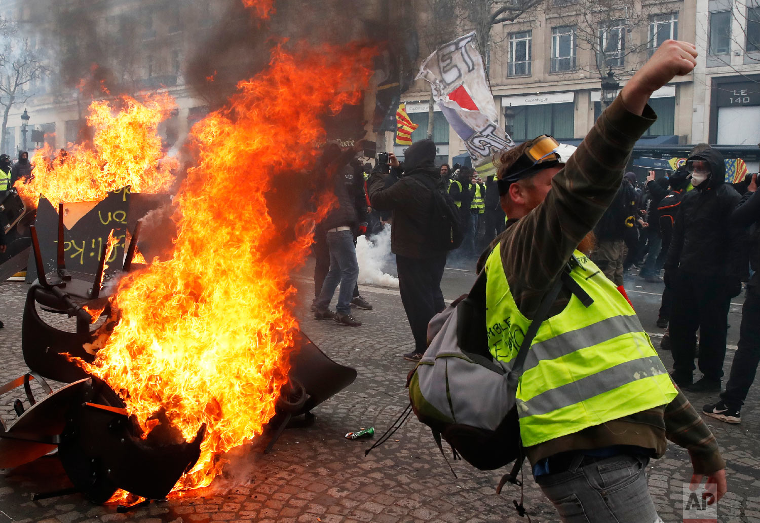 A protester shouts slogans in front of a barricade on fire during a yellow vests demonstration March 16, 2019, in Paris. (AP Photo/Christophe Ena)