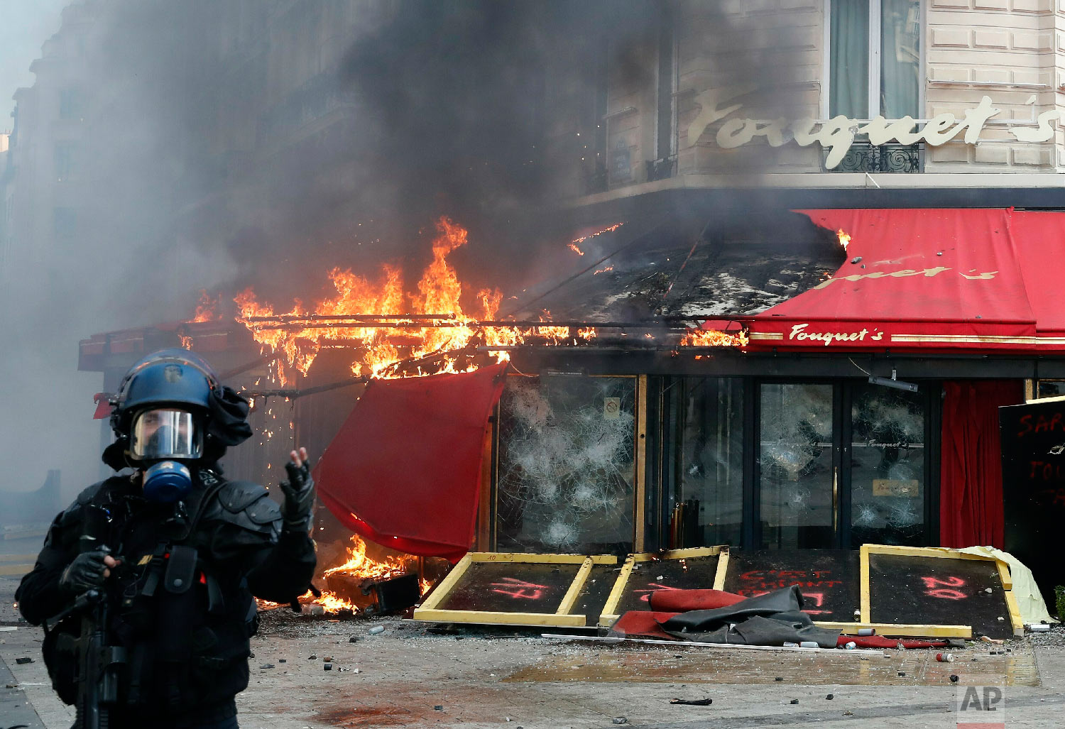 Paris famed restaurant Fouquet's burns on the Champs Elysees avenue during a yellow vests demonstration, March 16, 2019 in Paris. (AP Photo/Christophe Ena)