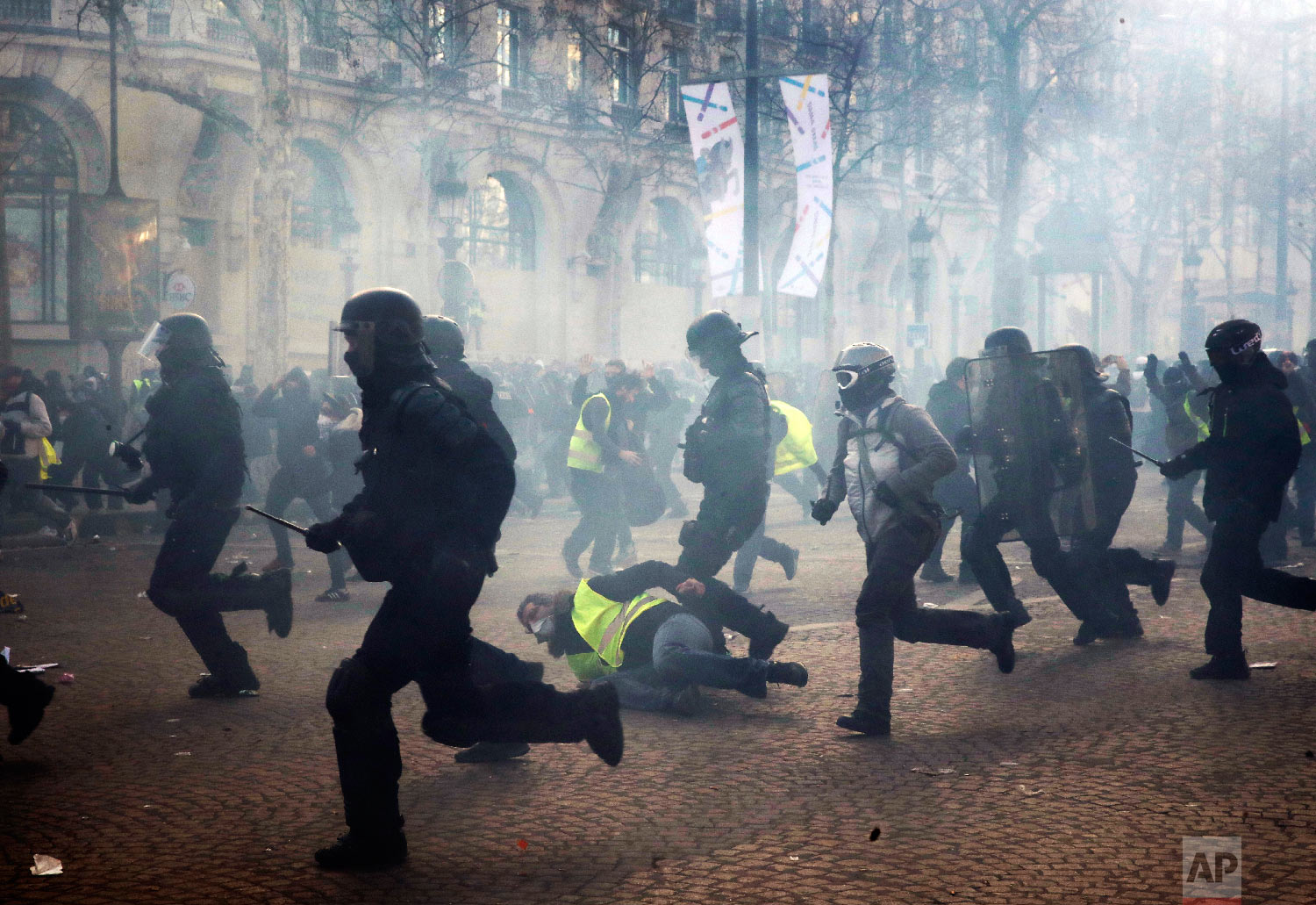 Riot police officers charge as a yellow vests demonstrator falls Saturday, March 16, 2019 in Paris. (AP Photo/Christophe Ena)