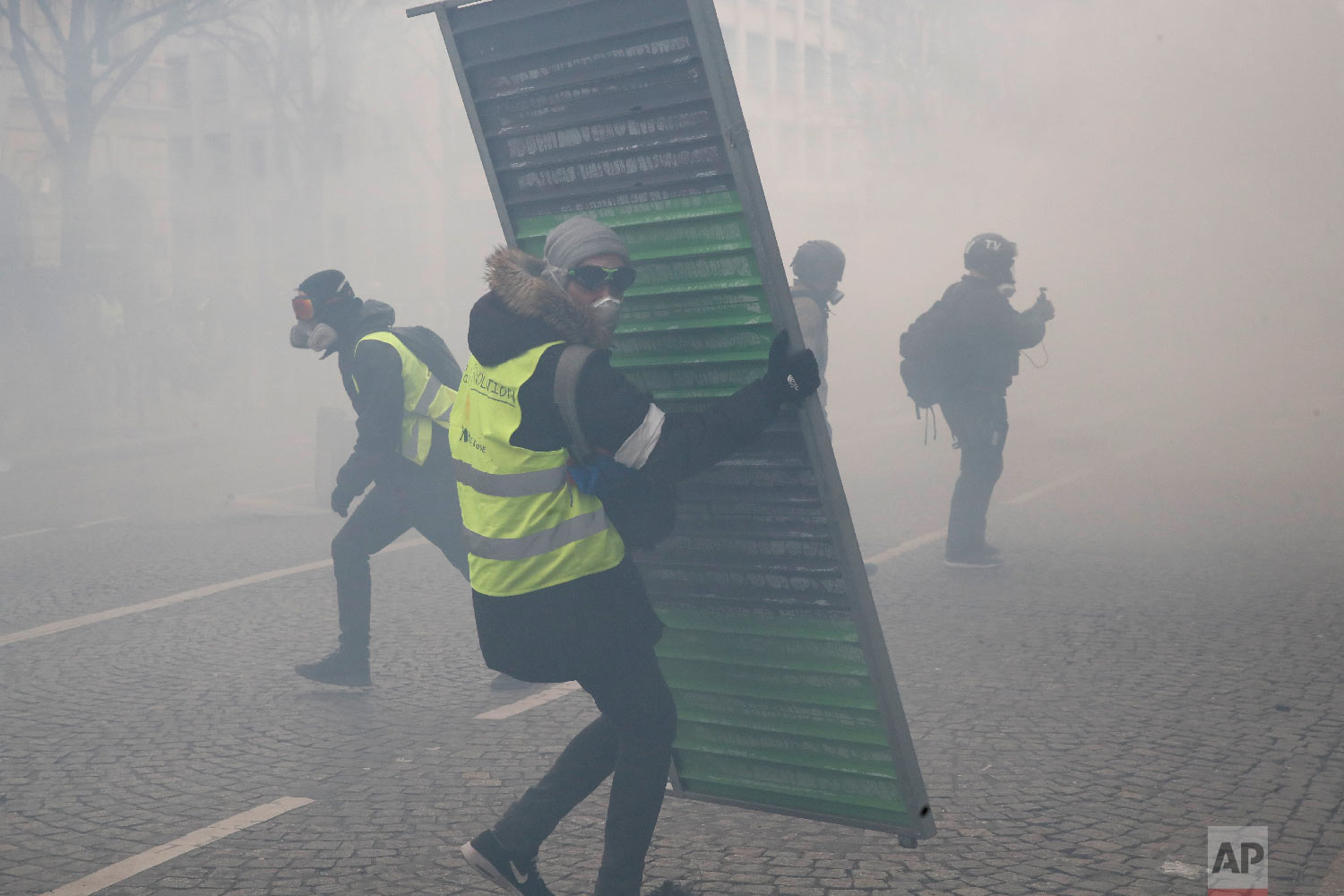 Protesters set up barricades through tear gas during a yellow vests demonstration, March 16, 2019. (AP Photo/Christophe Ena)