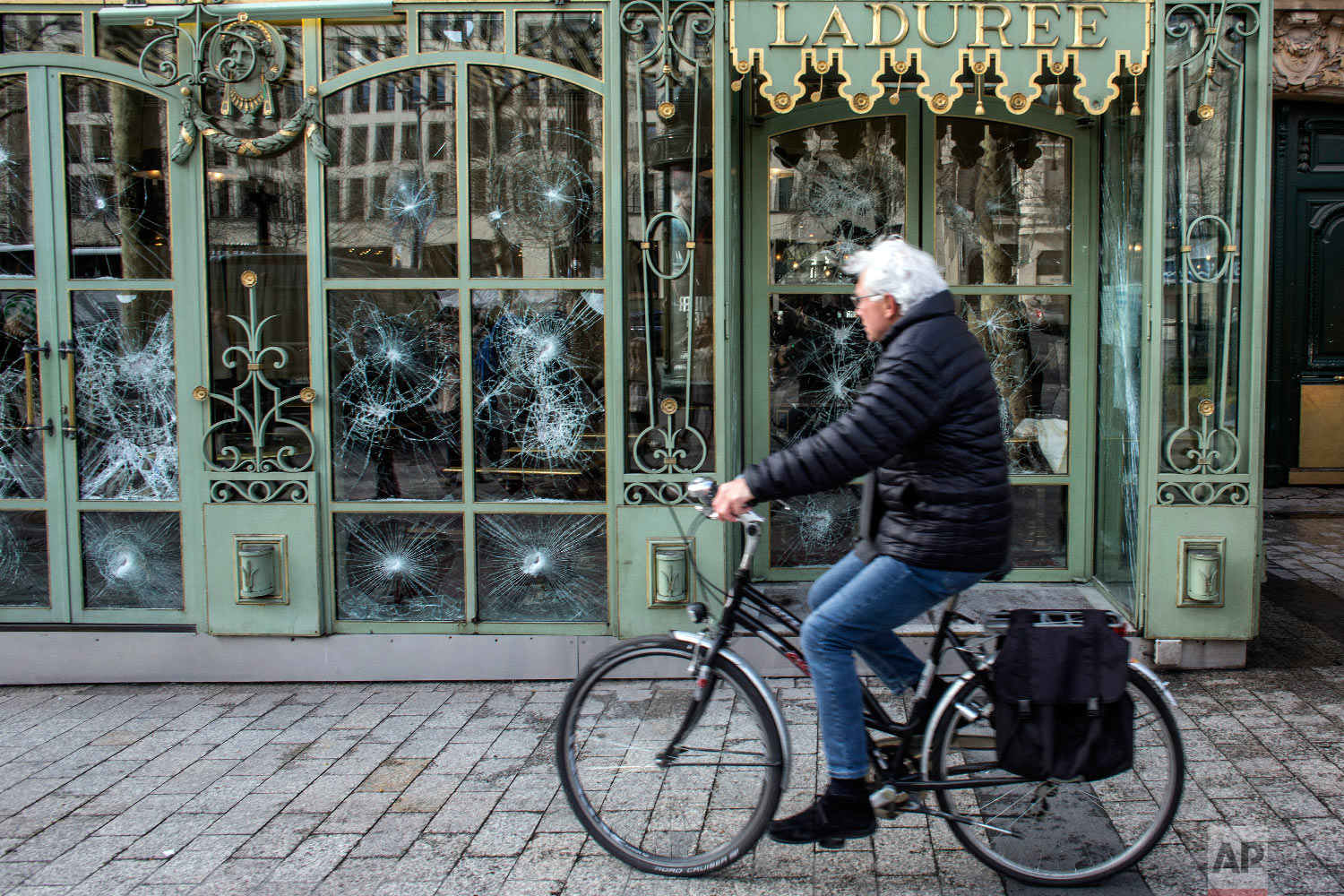 A cyclist rides past the smashed windows of the famed tea salon Laduree on the Champs Elysees the day after it was vandalized in Paris, France, March 17, 2019. (AP Photo/Rafael Yaghobzadeh)