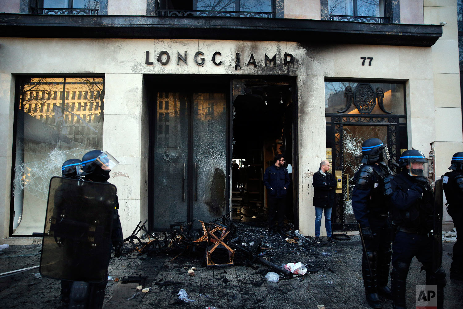 Riot policemen stand in front a burned store after a demonstration Saturday, March 16, 2019 in Paris. (AP Photo/Christophe Ena)