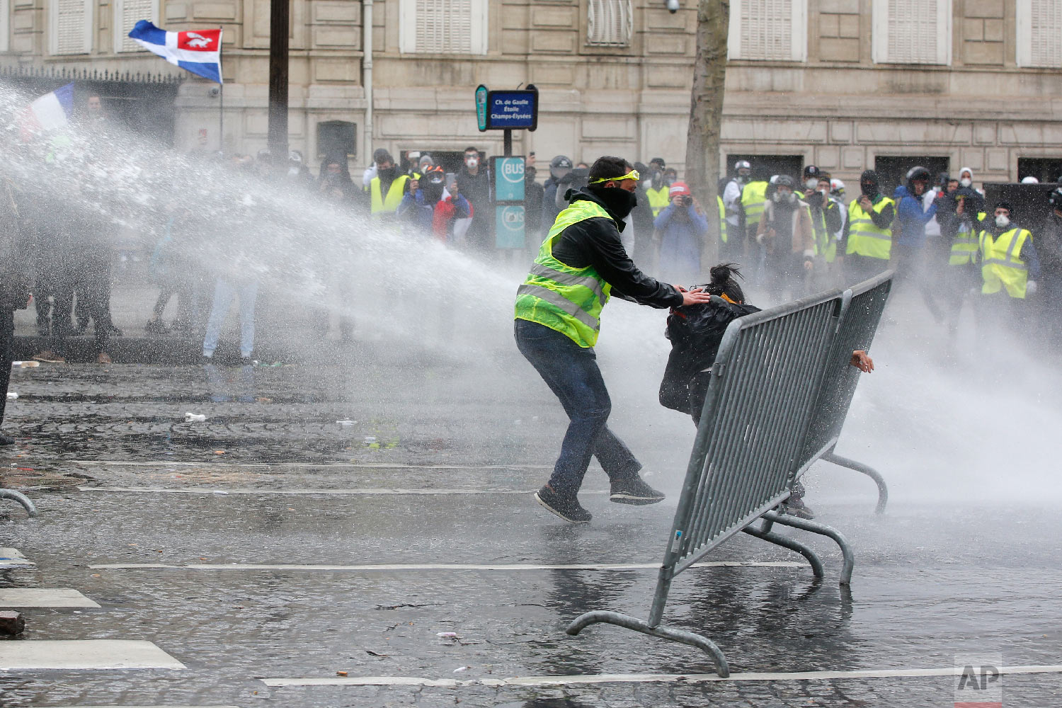 A yellow vests demonstrator rescues another one as police forces use water cannons, March 16, 2019, in Paris. (AP Photo/Christophe Ena)