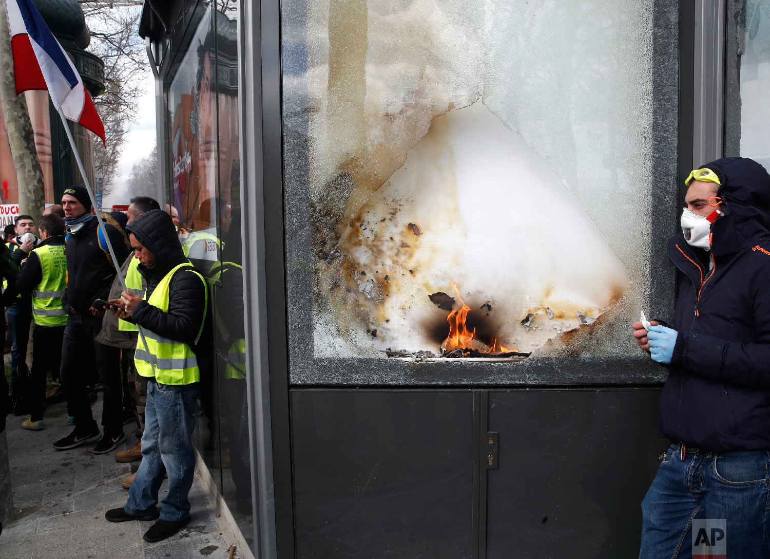 Yellow vests protesters stand by a damages shop during a demonstration, March 16, 2019. (AP Photo/Christophe Ena)
