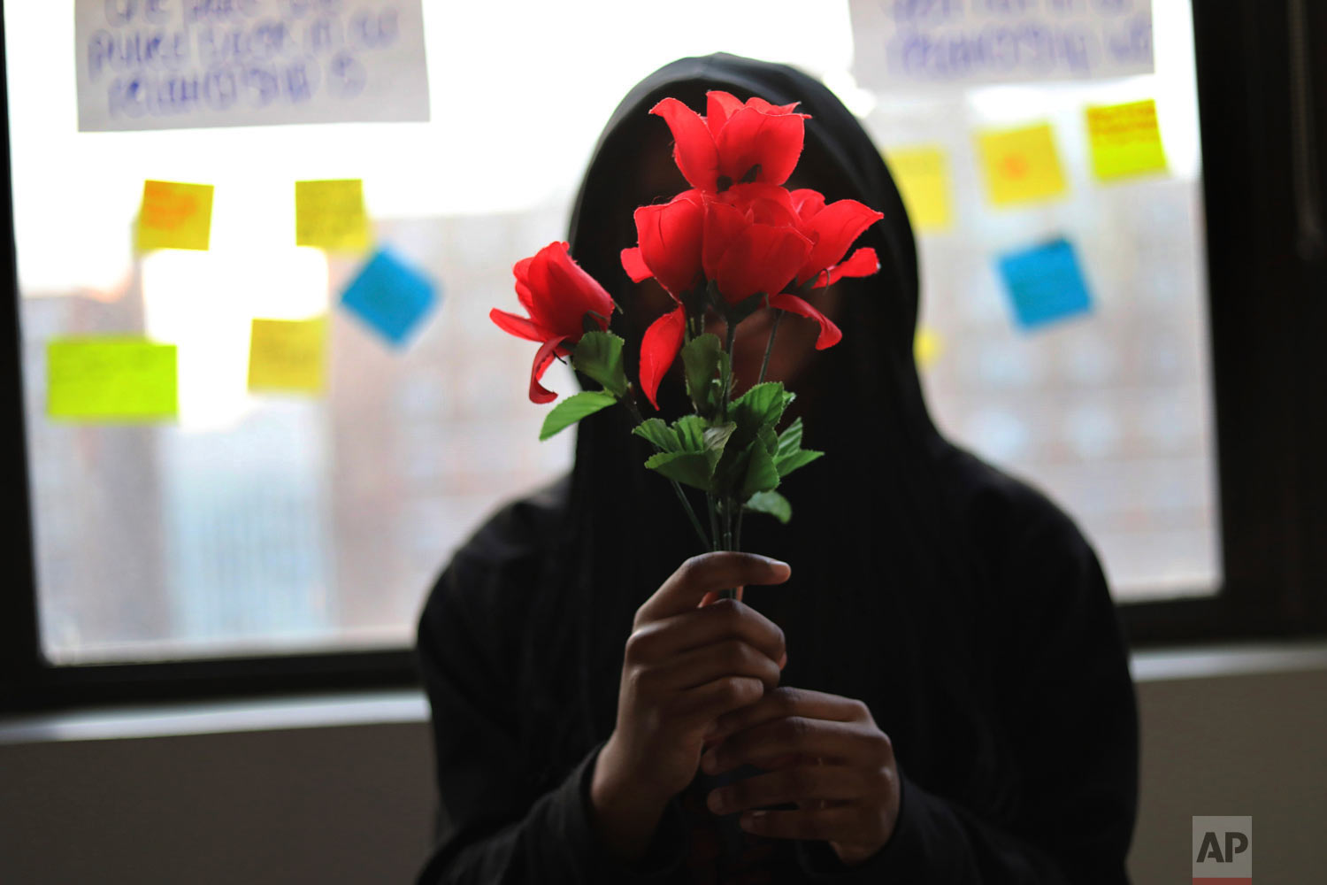 "A survivor of sexual assault holds plastic flowers after attending a meeting with the group ""Sisters in Strength"" in the Brooklyn borough of New York on Thursday, March 14, 2019. She said that she found refuge in two trusted teachers, who sent her to the support group run by the nonprofit Girls for Gender Equity. (AP Photo/Wong Maye-E)"