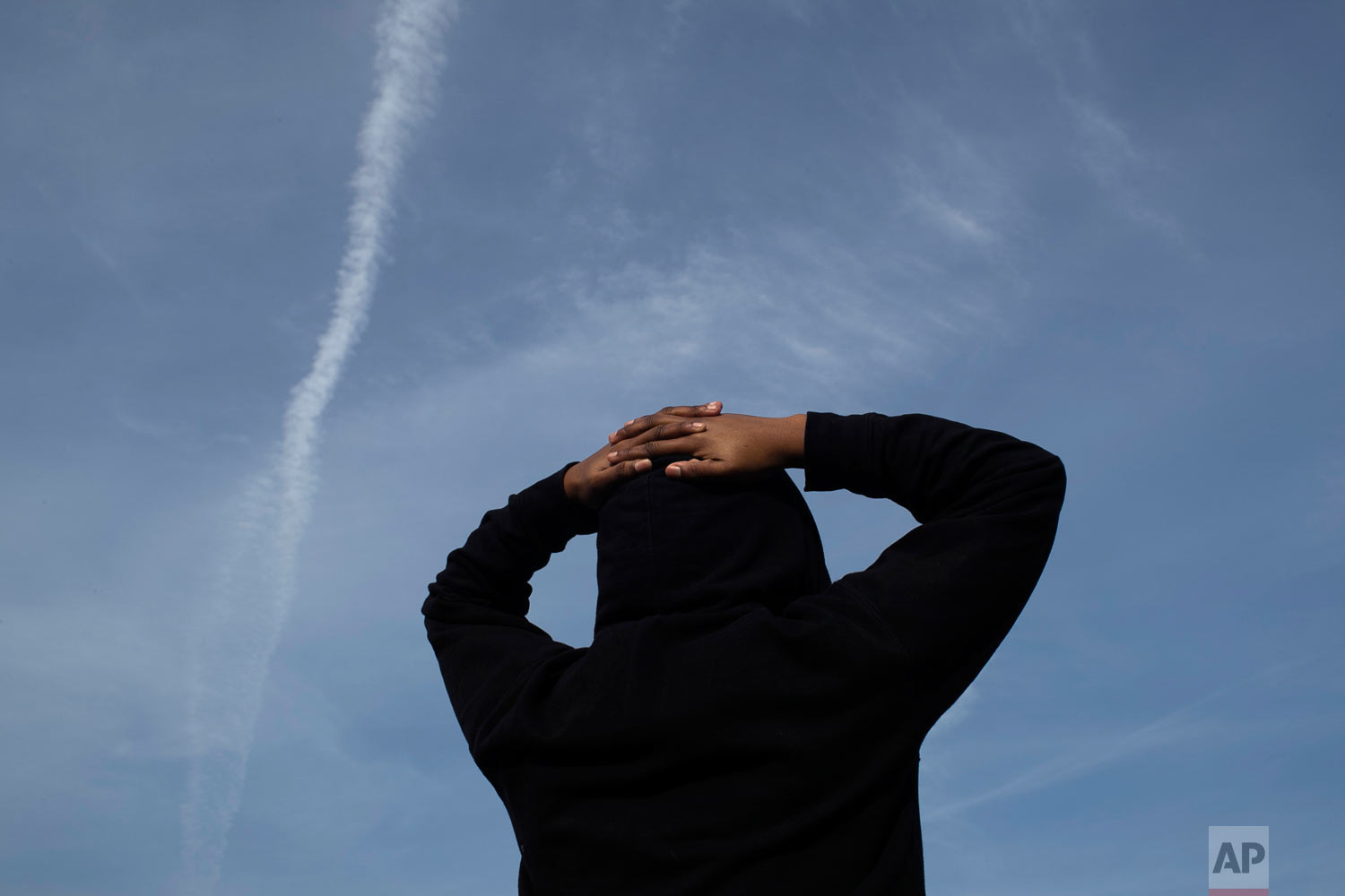 A survivor of sexual assault looks at the evening sky in the Brooklyn borough of New York on Thursday, March 14, 2019. The young woman seeks peace through meditation. She said that she was assaulted by someone she knew but never reported it because she feared she wouldn't be believed. (AP Photo/Wong Maye-E)