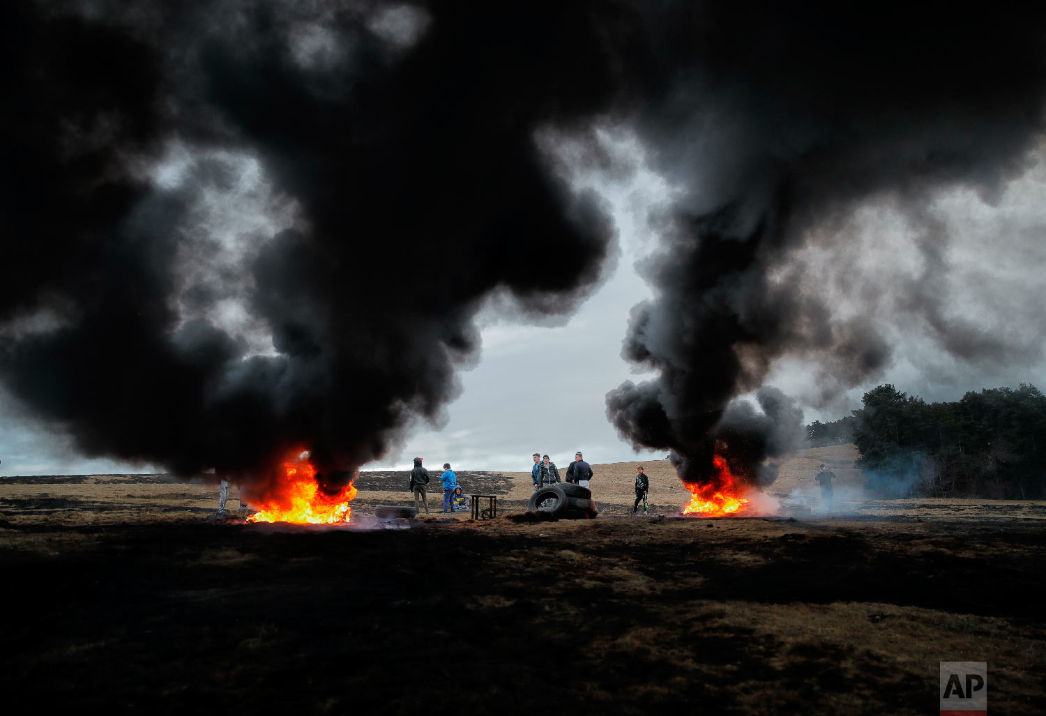 Children and youngsters stand by burning tires during a ritual marking the upcoming Clean Monday, the beginning of the Great Lent, 40 days ahead of Orthodox Easter, on the hills surrounding the village of Poplaca, in central Romania's Transylvania region, Sunday, March 10, 2019. (AP Photo/Vadim Ghirda)