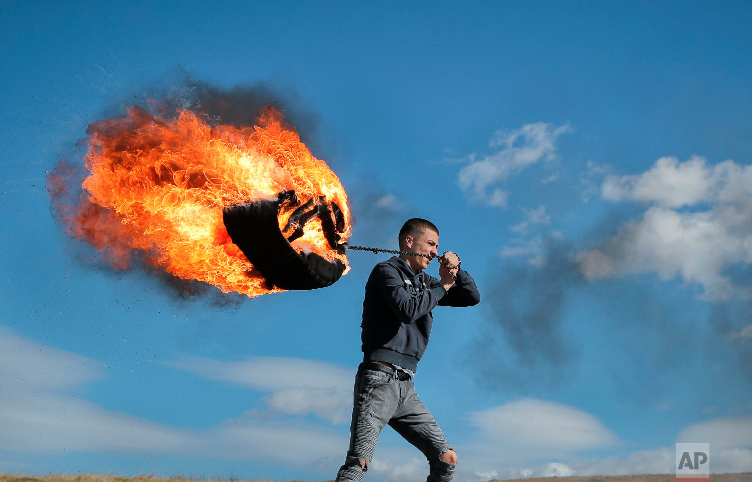 A young man spins a burning tire on a metal chain during a ritual marking the upcoming Clean Monday, the beginning of the Great Lent, 40 days ahead of Orthodox Easter, on the hills surrounding the village of Poplaca, in central Romania's Transylvania region, Sunday, March 10, 2019. (AP Photo/Vadim Ghirda)